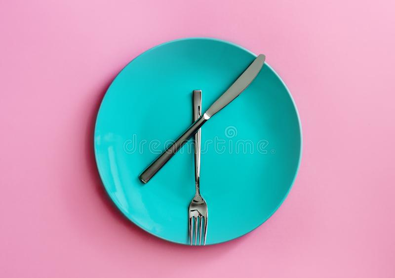 Placa verde limpia y cuchillo y bifurcaci?n inoxidables en fondo rosado Hora de comer Visi?n superior foto de archivo