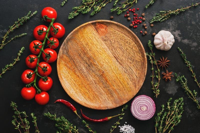 Placa, verduras, especias e hierbas de madera vacías puestas plano en fondo de piedra oscuro Tomates, tomillo, ajo, grano de pimi foto de archivo