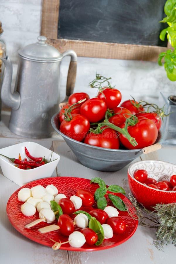 Placa vermelha com tomates e a mussarela pequenos imagem de stock