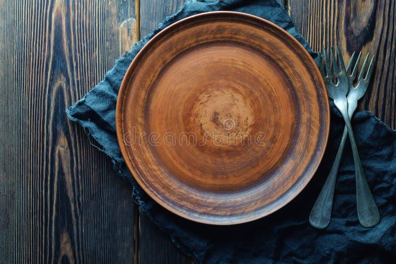 Placa y bifurcaciones rústicas limpias en un fondo de madera fotografía de archivo