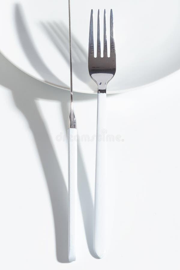 Placa y cubiertos blancos en una tabla ligera Concepto minimalistic de Cretive foto de archivo libre de regalías