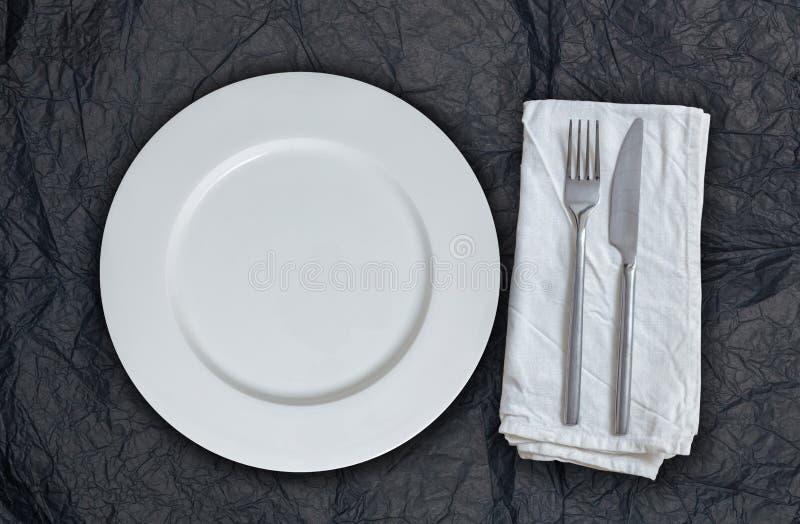 Placa y cubiertos vacíos en el papel seda negro fotografía de archivo