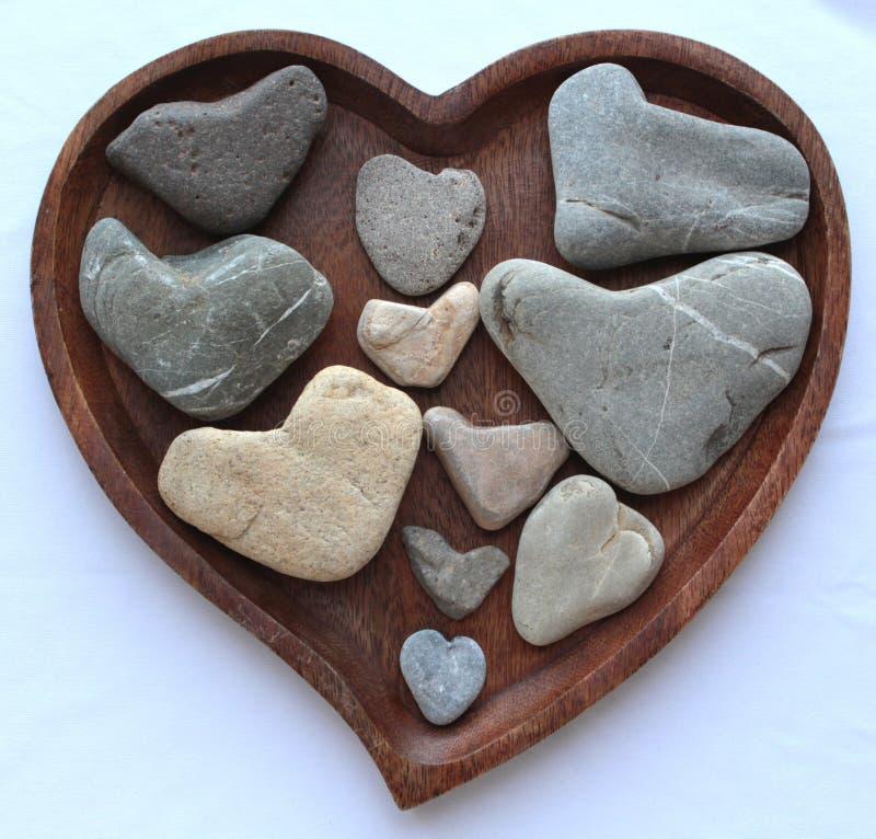 Placa y piedras de madera en forma de corazón fotos de archivo