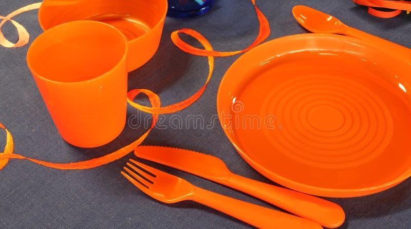 Placas anaranjadas en la tabla preparada para celebrar un cumpleaños fotografía de archivo libre de regalías