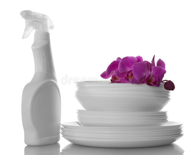 Placas blancas lavadas, detergente del lavaplatos y una rama de la orquídea aislada en blanco foto de archivo libre de regalías