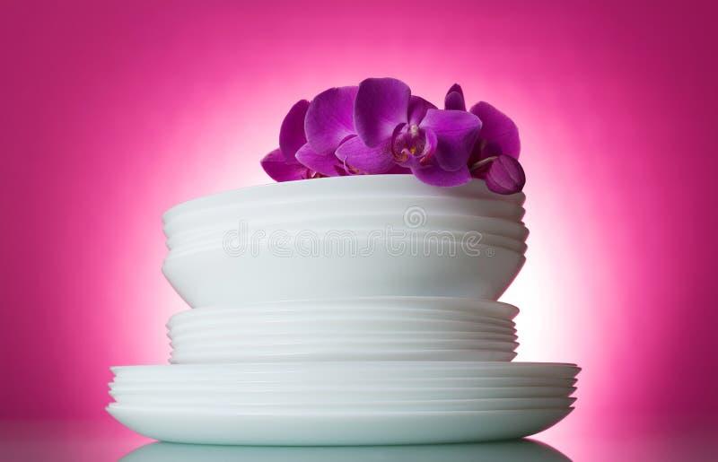 Placas blancas lavadas limpias en fondo rosado y una rama de la orquídea fotografía de archivo libre de regalías