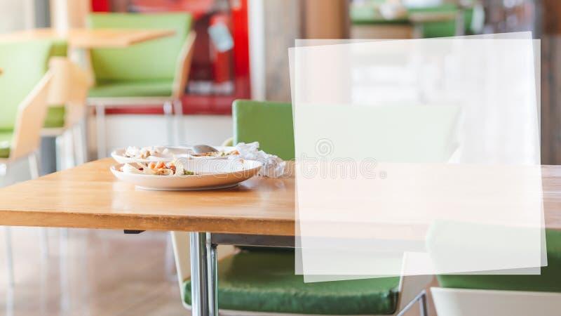 Placas brancas com o alimento restante e os alguns lixos na tabela de madeira com a caixa de texto branca fotos de stock