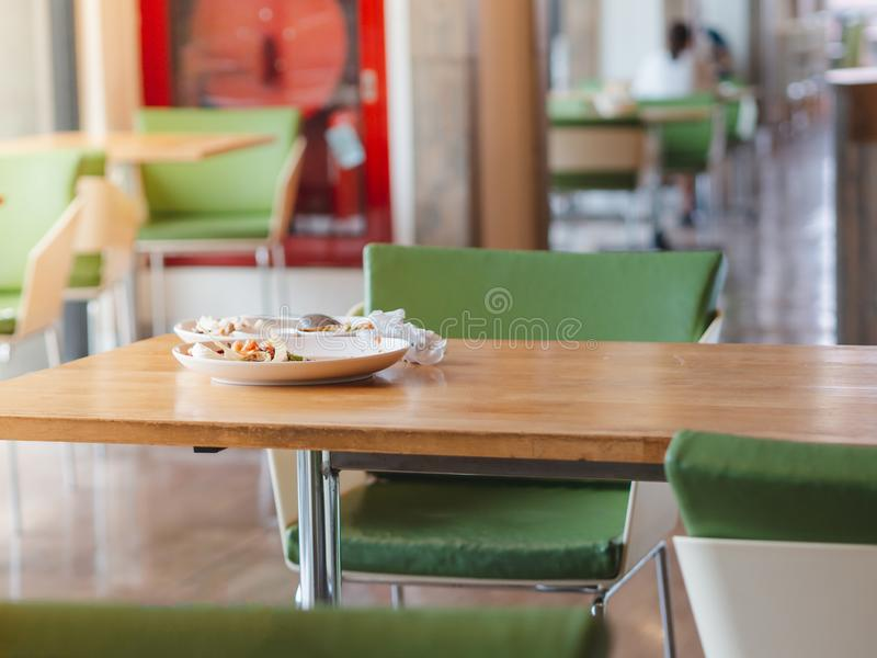 Placas brancas com o alimento restante e os alguns lixos na tabela de madeira fotos de stock royalty free