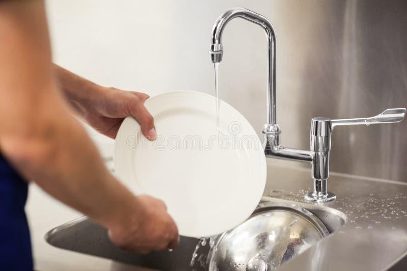 Placas brancas de limpeza do porteiro da cozinha no dissipador imagens de stock royalty free