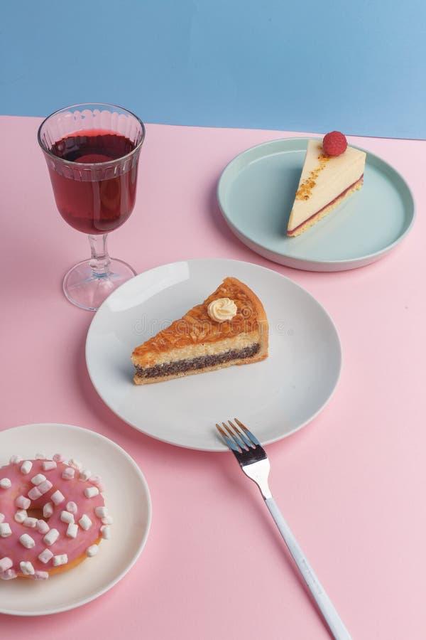 Placas con el pastel de queso y el vidrio deliciosos con una bebida en un fondo rosado fotografía de archivo libre de regalías
