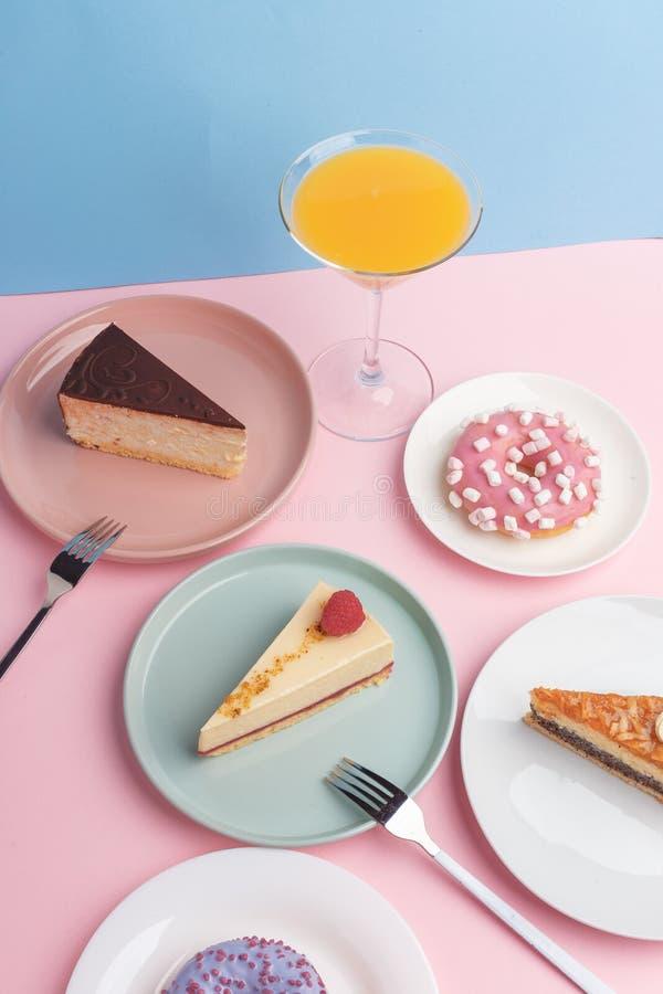 Placas con el pastel de queso y el vidrio deliciosos con una bebida en un fondo rosado foto de archivo libre de regalías