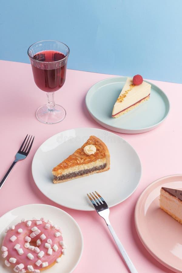 Placas con el pastel de queso y el vidrio deliciosos con una bebida en un fondo rosado imagen de archivo