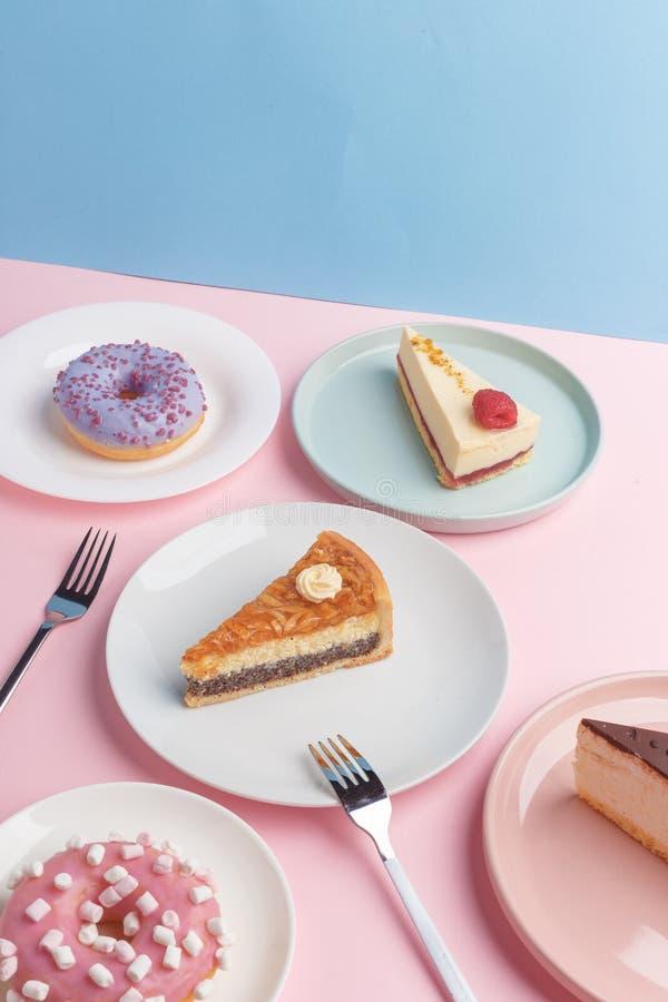 Placas con el pastel de queso y el vidrio deliciosos con una bebida en un fondo rosado imagenes de archivo