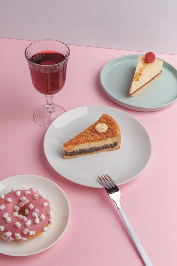 Placas con el pastel de queso y el vidrio deliciosos con una bebida en un fondo rosado imágenes de archivo libres de regalías