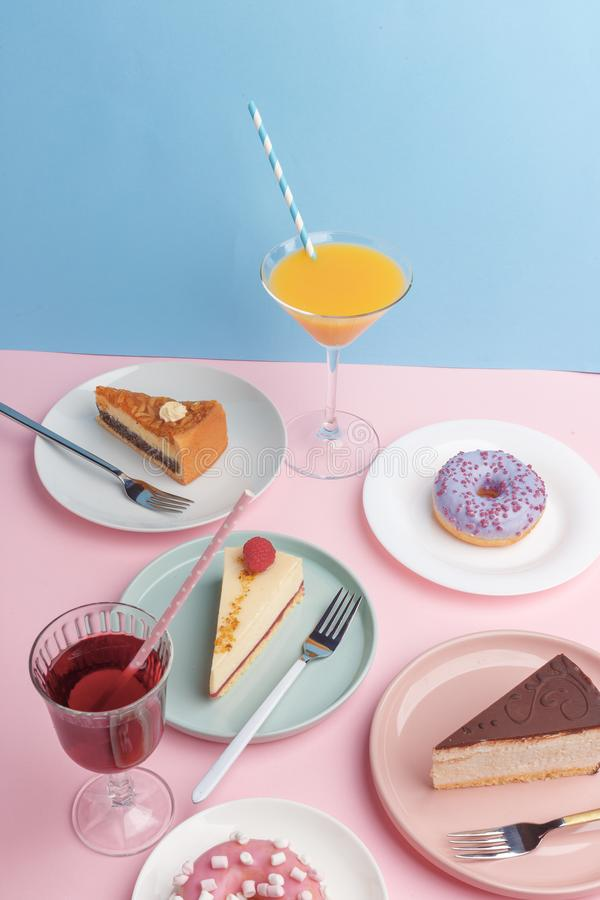 Placas con el pastel de queso y el vidrio deliciosos con una bebida en un fondo rosado foto de archivo