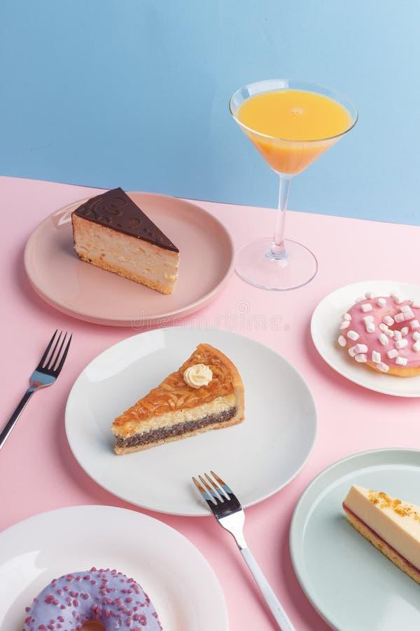 Placas con el pastel de queso y el vidrio deliciosos con una bebida en un fondo rosado fotos de archivo libres de regalías