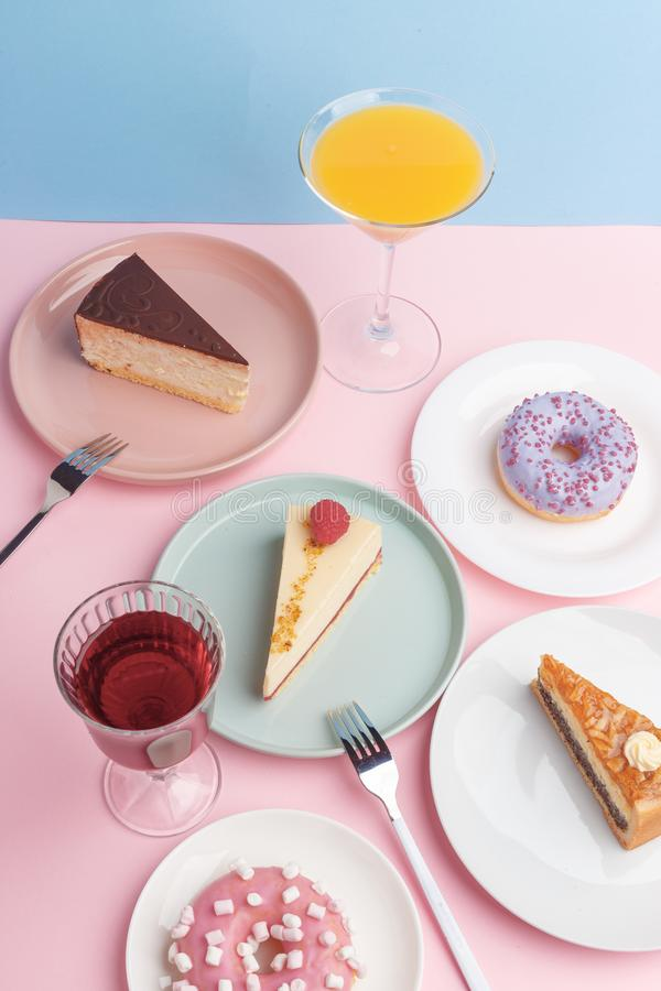 Placas con el pastel de queso y el vidrio deliciosos con una bebida en un fondo rosado imagen de archivo libre de regalías