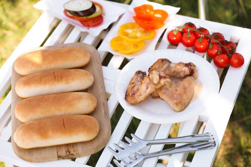 Placas con las alas, las verduras y el pan asados a la parrilla de pollo en la tabla al aire libre preparada para la comida campe fotografía de archivo libre de regalías