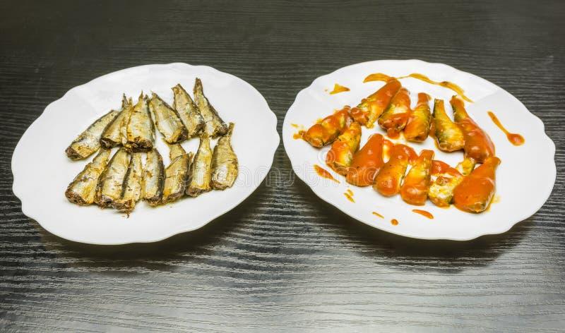 Placas con los espadines ahumados en salsa del aceite y de tomate imagenes de archivo
