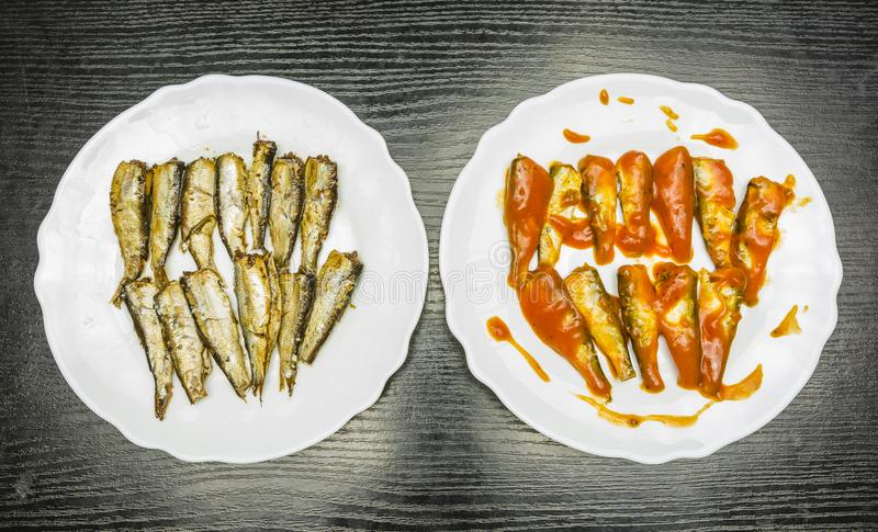 Placas con los espadines ahumados con la salsa del aceite y de tomate Visión desde arriba fotografía de archivo libre de regalías