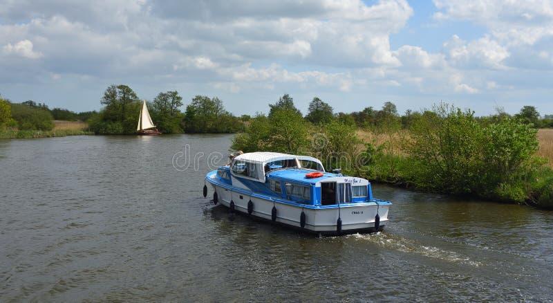 Placas cruzador e iate sob a vela que navega o rio Bure perto de Horning, o Norfolk Broads fotografia de stock