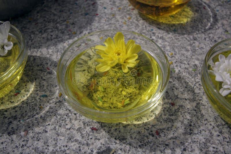 Placas de cristal con aceite y flores amarillas en la tabla del granito fotografía de archivo libre de regalías