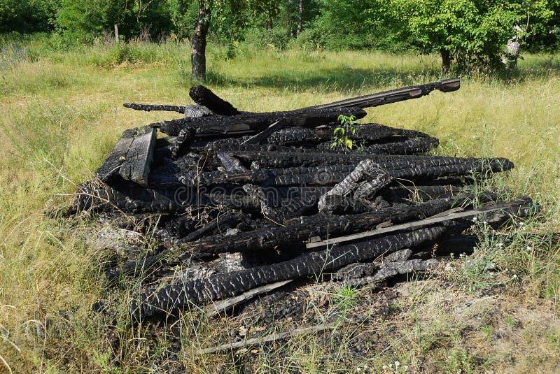 placas de madeira queimadas em uma mentira do montão na grama verde imagem de stock royalty free