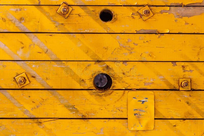 Placas de madeira velhas pintadas amarelo com furos Textura de madeira natural abstraia o fundo fotografia de stock