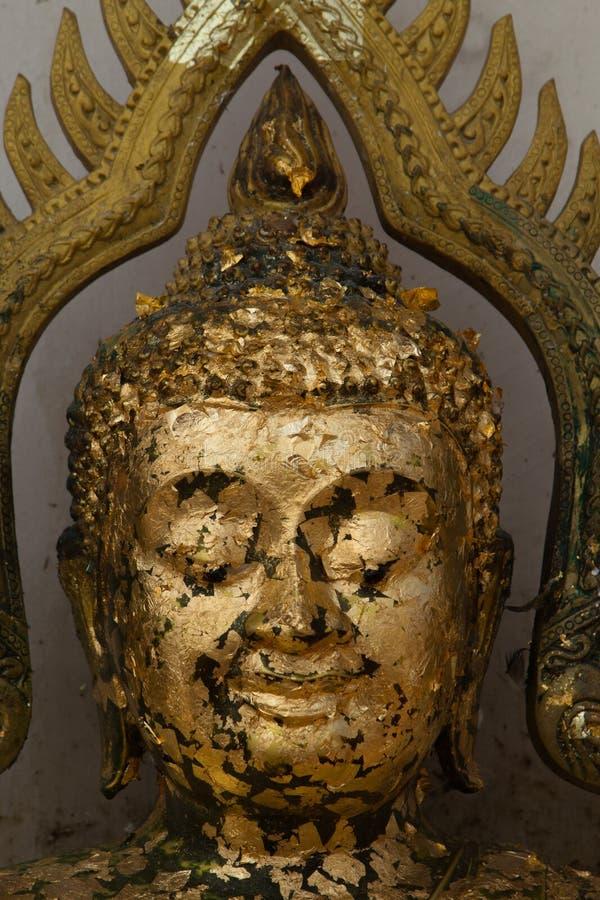Placas de oro en la cara Buda, la estatua de Buda a dorar con el oro l fotos de archivo