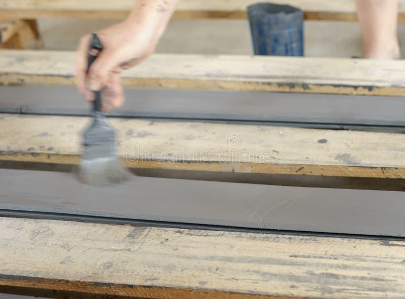 Placas de pintura com uma escova guardada à disposição Cinza, pintura de madeira antracífera fotografia de stock