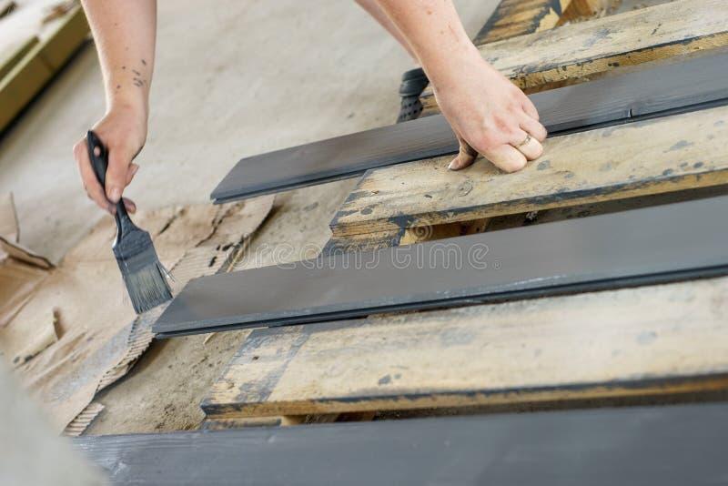 Placas de pintura com uma escova guardada à disposição Cinza, pintura de madeira antracífera imagem de stock