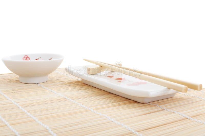 Placas e chopsticks do sushi na esteira de bambu fotos de stock royalty free