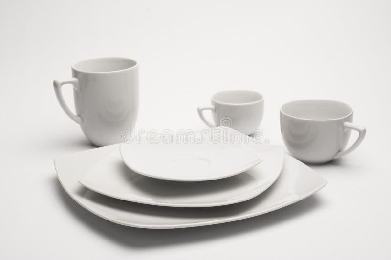 Placas e copos brancos fotografia de stock royalty free