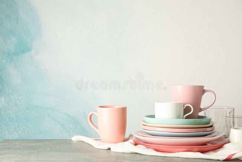 Placas e copos da cor empilhados na tabela cinzenta fotografia de stock royalty free