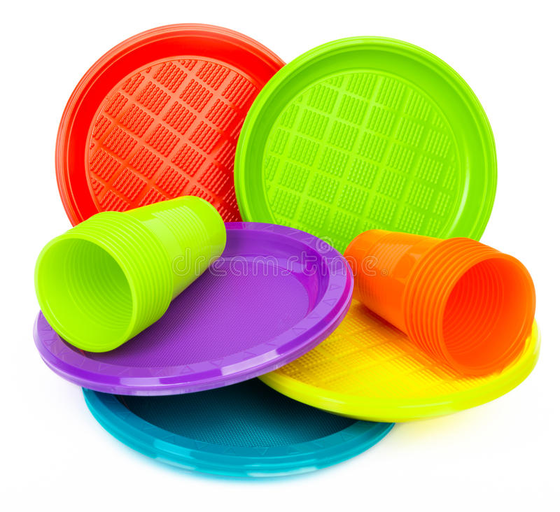 Placas e copos plásticos brilhantes descartáveis no branco foto de stock royalty free