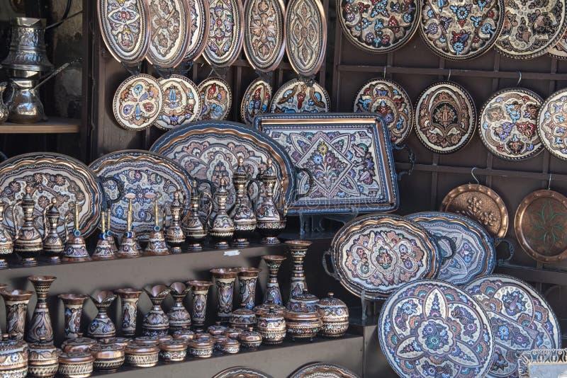 Placas esmaltadas decorativas en venta a los turistas en un bazar local de la calle foto de archivo
