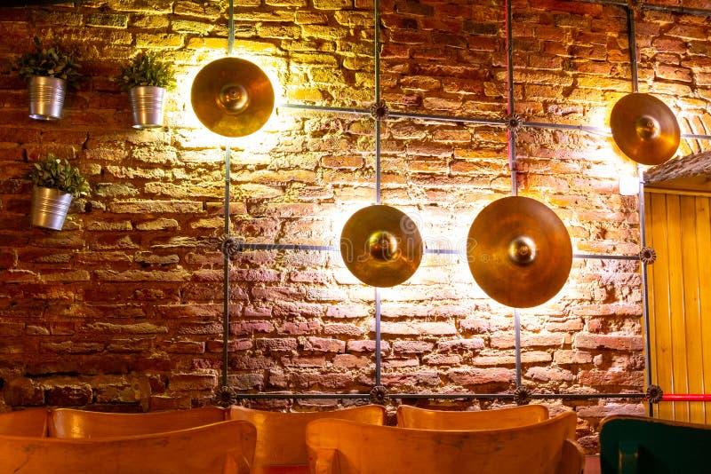 Placas iluminadas retroiluminadas dos pratos que ornamenting uma parede de tijolo, com as flores artificiais verdes que penduram  fotografia de stock royalty free