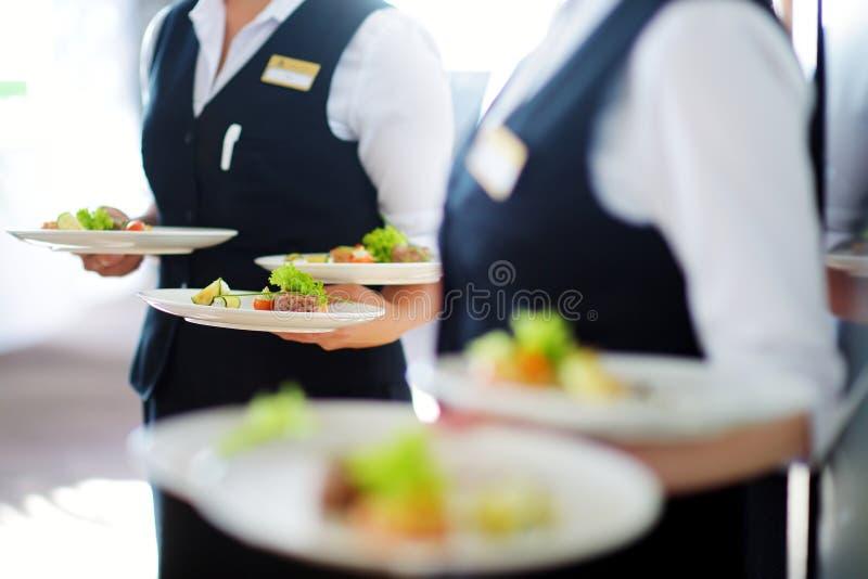 Placas levando do garçom com o prato da carne em algum evento festivo fotografia de stock