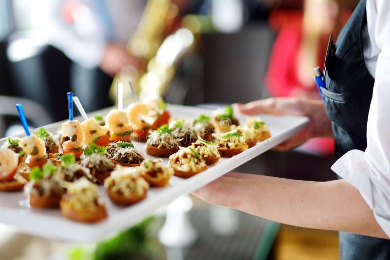 Placas levando do garçom com o prato da carne no evento, no partido ou no copo de água festivo fotografia de stock