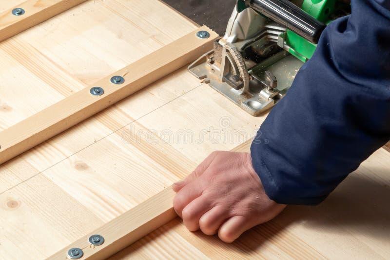 Placas masculinas ver de mãos com uma serra de circular fotografia de stock
