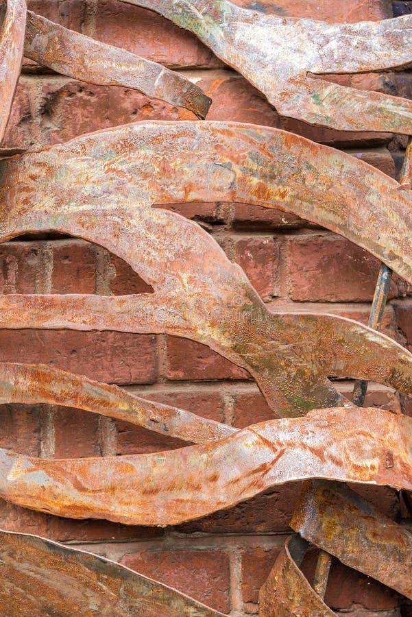 Placas torcidas e oxidadas do ferro em uma parede de tijolo velha fotografia de stock royalty free