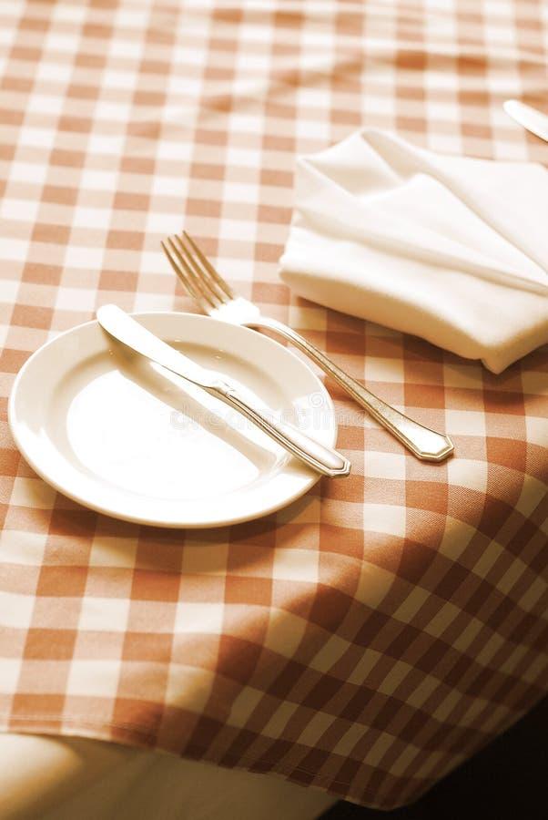 Placas vazias brancas com forquilha e faca em uma toalha de mesa vermelha fotos de stock royalty free