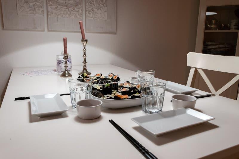 Placas y platos en la tabla en un apartamento el uno mismo hizo el rollo de sushi Cena romántica con la luz ambiente de la vela fotografía de archivo