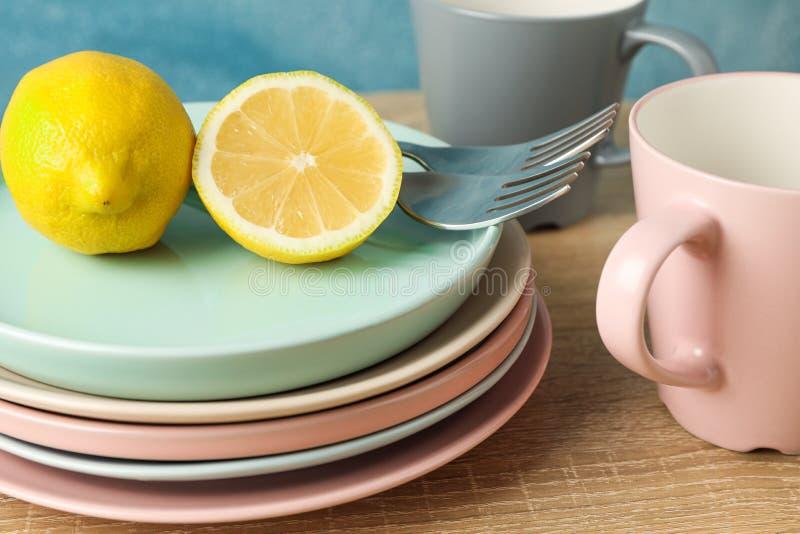 Placas y tazas con los limones apilados en la tabla de madera imagen de archivo libre de regalías