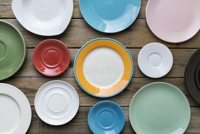 Placas y utensilio vacíos del color en fondo de madera de la tabla imagenes de archivo