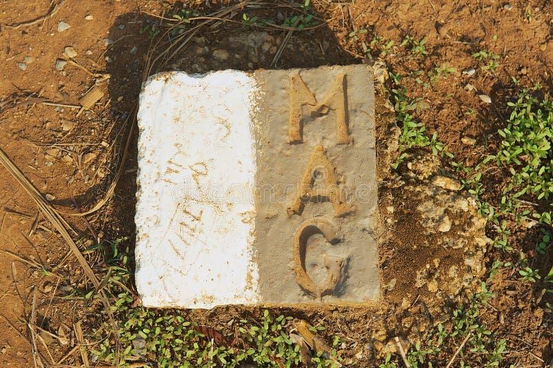 Placca di pietra dal gruppo consultivo delle miniere che segna la posizione della bomba inesplosa resa sicuro in Phonsavan, Laos fotografia stock libera da diritti