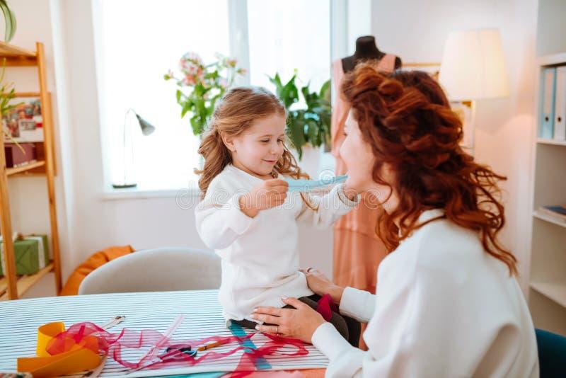 Placcatura sveglia allegra della figlia nell'atelier di sua madre che la visita fotografia stock libera da diritti