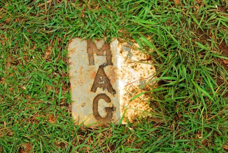 Placche di pietra dal segno di gruppo consultivo delle miniere la posizione delle bombe inesplose rese sicuro nella pianura del s fotografia stock libera da diritti
