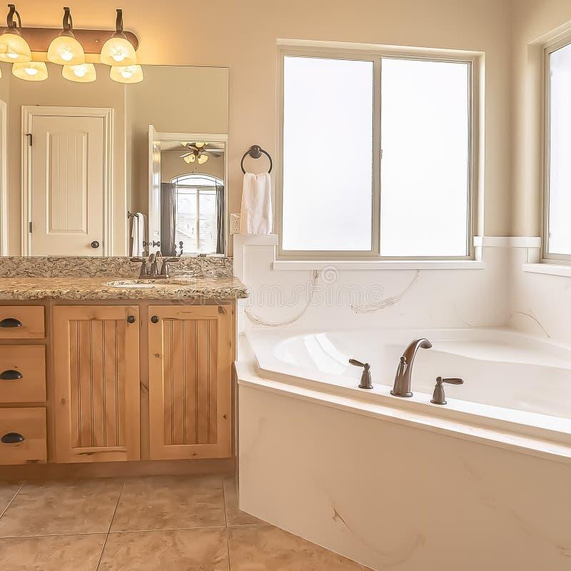 Place établie dans la baignoire au coin d'une salle de bains à la maison avec le plancher de tuiles et le mur beige photographie stock libre de droits