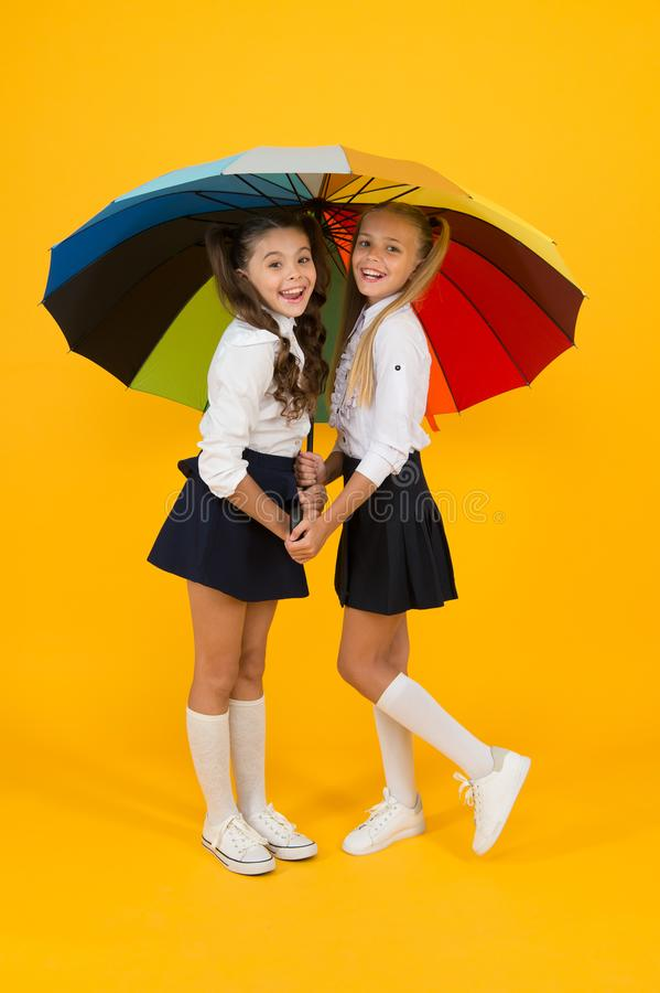 Place for both of us. Fashion accessory. Girls friends with umbrella. Rainy day. Happy childhood. School time. Rainbow. Umbrella. Colorful life. Schoolgirls royalty free stock image